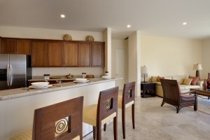 Ange of kitchen counter and bar chairs with view of living room